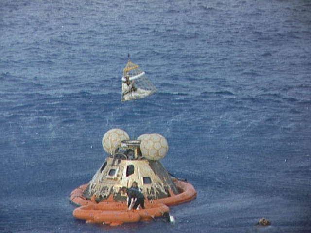 "Astronaut John L. Swigert Jr., Apollo 13 command module pilot, is lifted  aboard a helicopter in a ""Billy Pugh"" net while Astronaut James A. Lovell  Jr., commander, awaits his turn. Astronaut Fred Haise Jr., lunar module  pilot, is already aboard the helicopter. In the life raft with Lovell and in the water are several U.S. Navy Underwater Demolition Team Swimmers who  assisted in the recovery operations. The Apollo 13 spacecraft splashed down  at 12:07:44 p.m., April 17, 1970."
